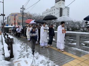 雪の中お寺へ向かう行列